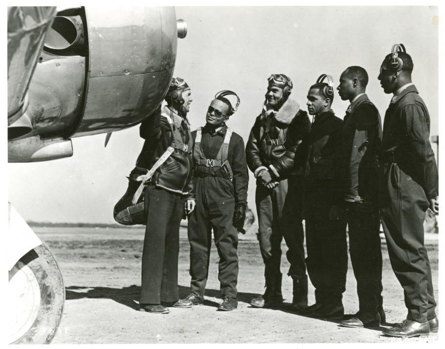 Five men look at an airplane