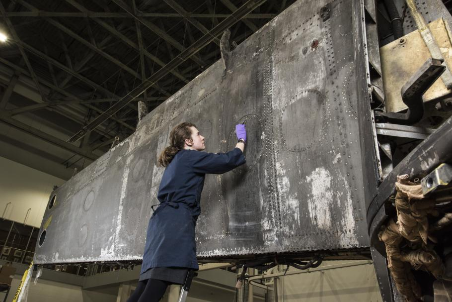 woman looks at aircraft paint