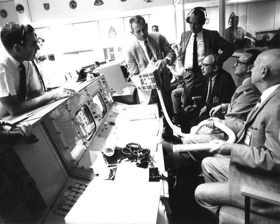 group of men around mission control desk