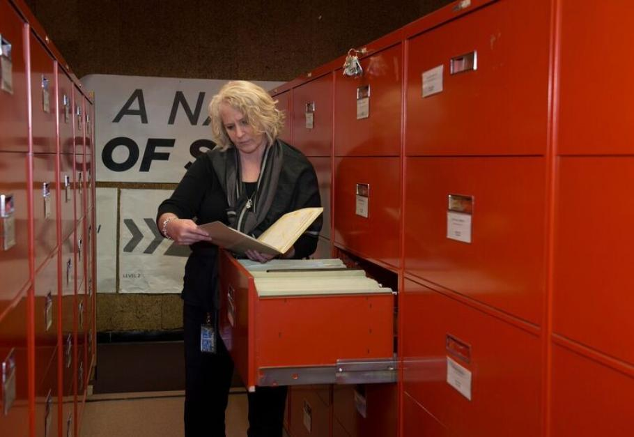 An archivist looks at a file while standing in front of a filing cabinet.