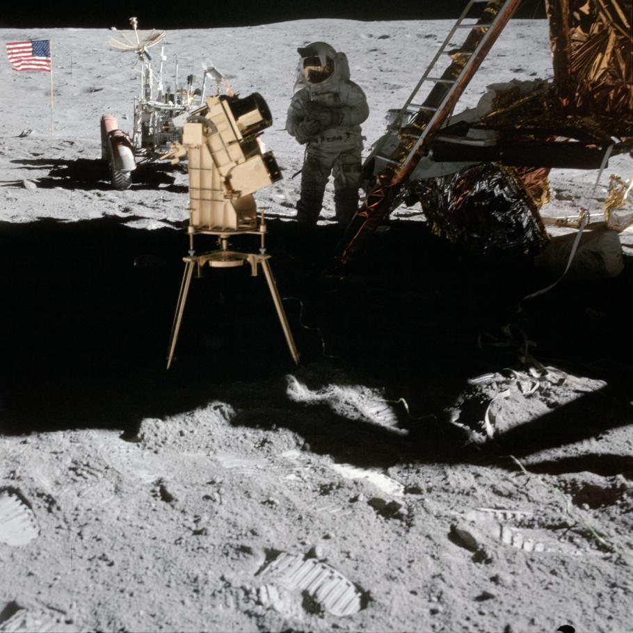 Image of camera on the Moon; Lunar Module, Astronaut, and American flag in background.