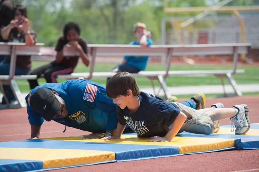 An astronaut and a student do push-ups outside.