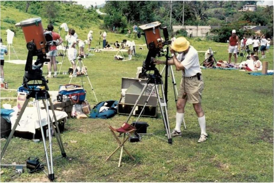 Man peers into a telescope at a large field.