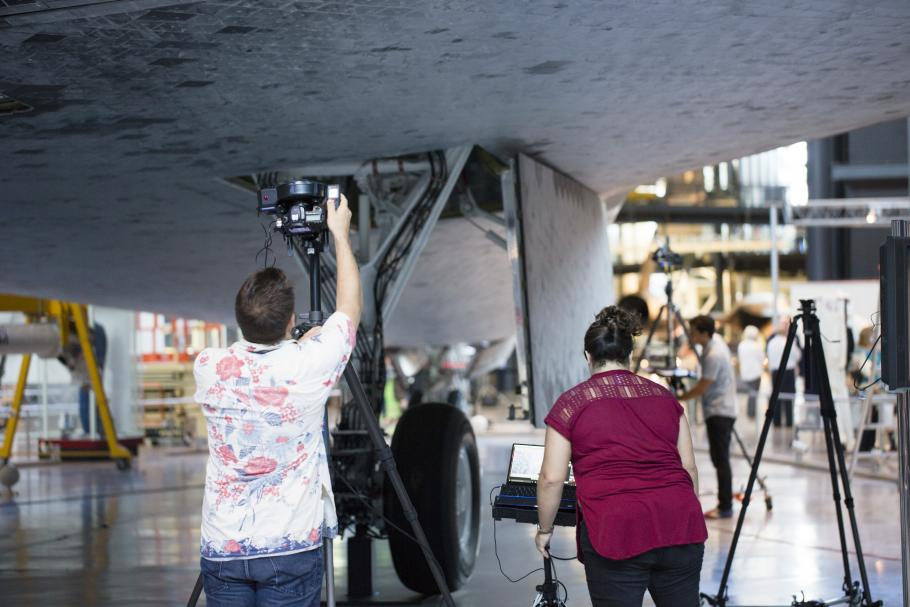 two people stand under Discovery's wing with photo equipment