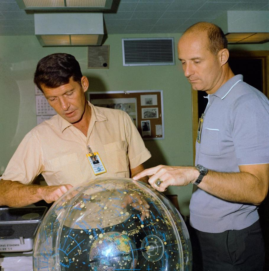 Astronauts Wally Schirra and Thomas Stafford, examine a star globe ahead of their upcoming Gemini VI mission