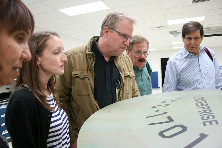 Denise Okuda, Ariel O'Connor, John Goodson, Rick Sternbach, and Adam Schneider study the original weathering streaks that had been subtly painted on the top of the saucer prior to filming