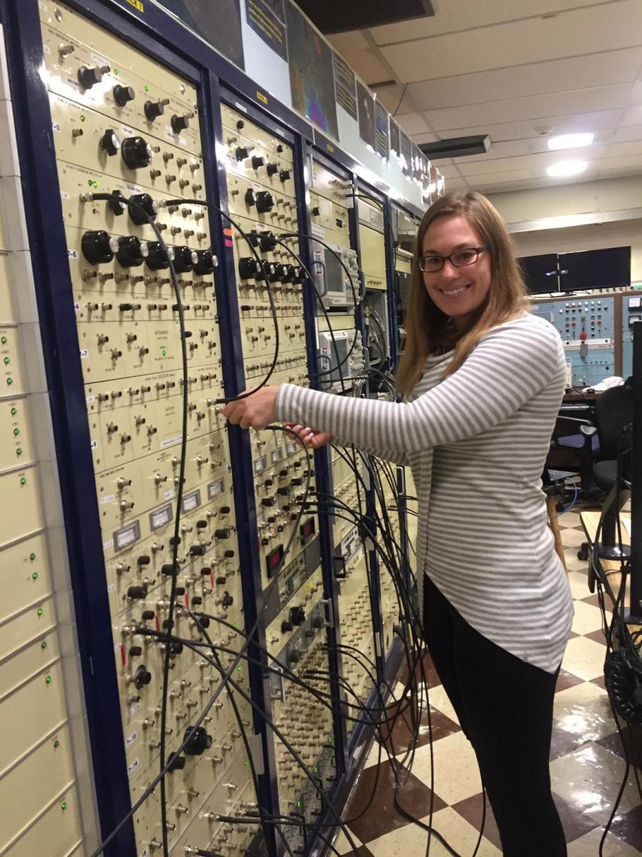 Woman stands in front of a large control board with multiple wires and access points.