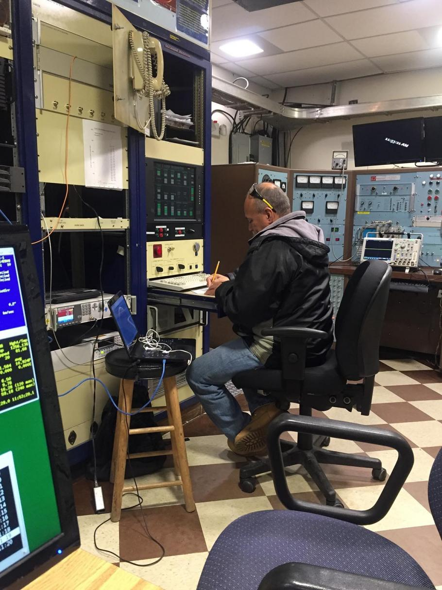 Man works at a small desk surrounded by equipment.