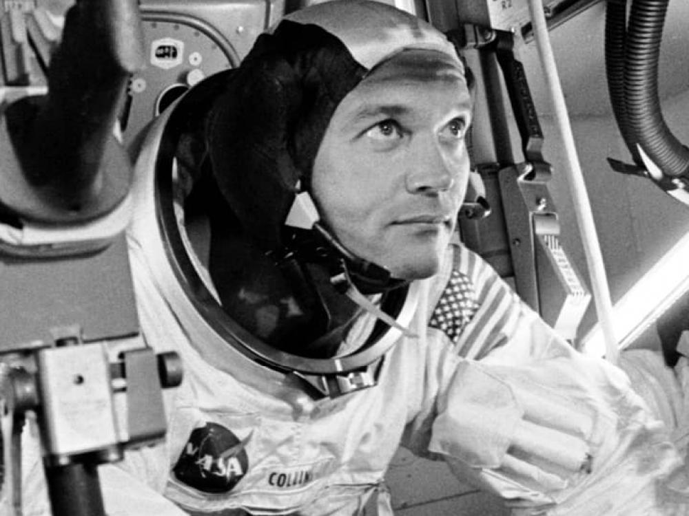 A man, Michael Collins, in a space suit looking out.