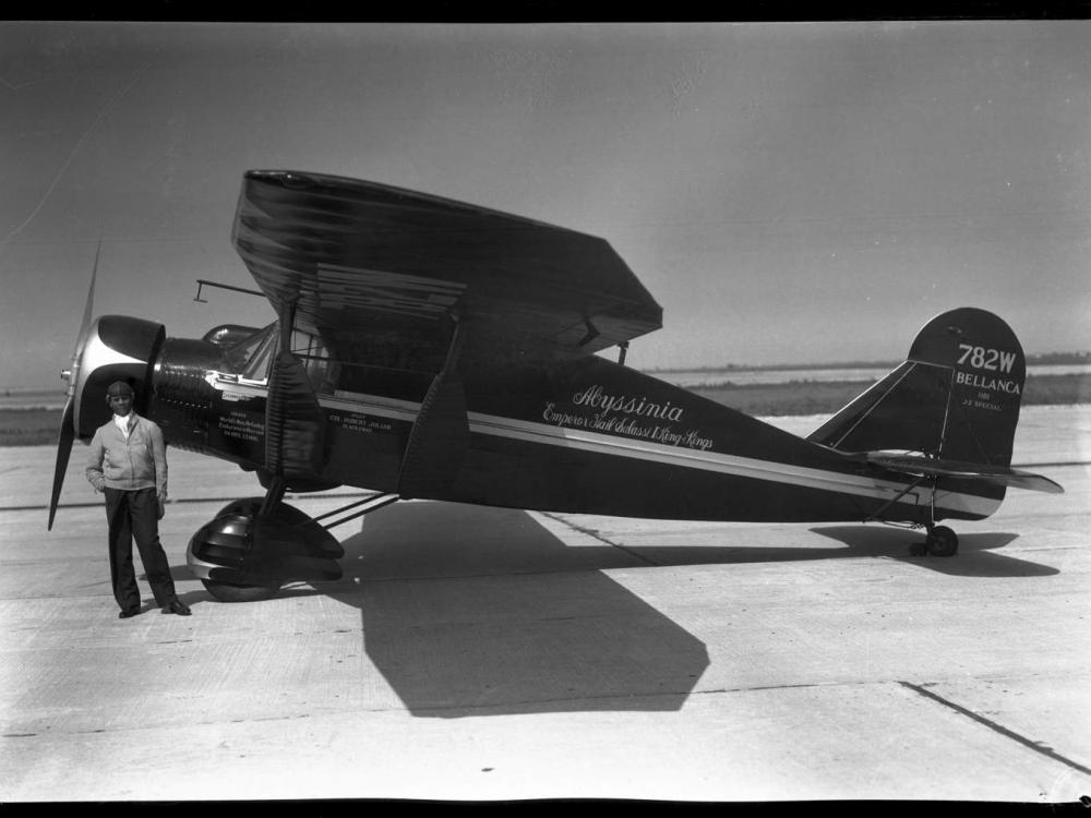 "Black and white left side view of monoplane painted black with white stripe down middle. Cursive handwritten text in center of plane reads: ""Abyssinia Emperor Haile Salassi I King of Kings."" Tail text ""782W/Bellanca"" Black man by nose right hand in pocket"