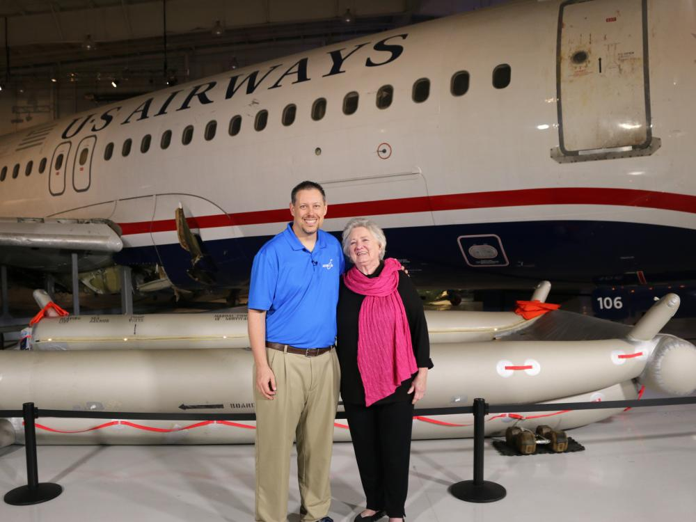 Two people stand in front of an aircraft.
