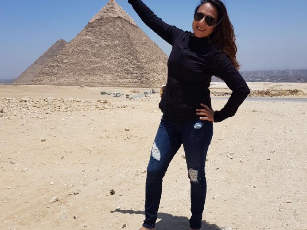 Pilot Shaesta Waiz in Egypt appearing to touch the top of a pyramid that's in the distance.
