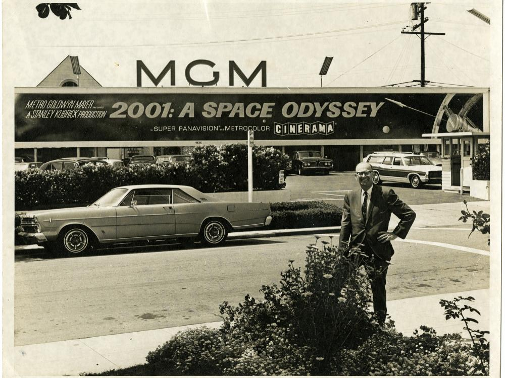 "Arthur C. Clarke poses for a photo beneath a sign advertising the motion picture ""2001: A Space Odyssey,"" May 16, 1968."