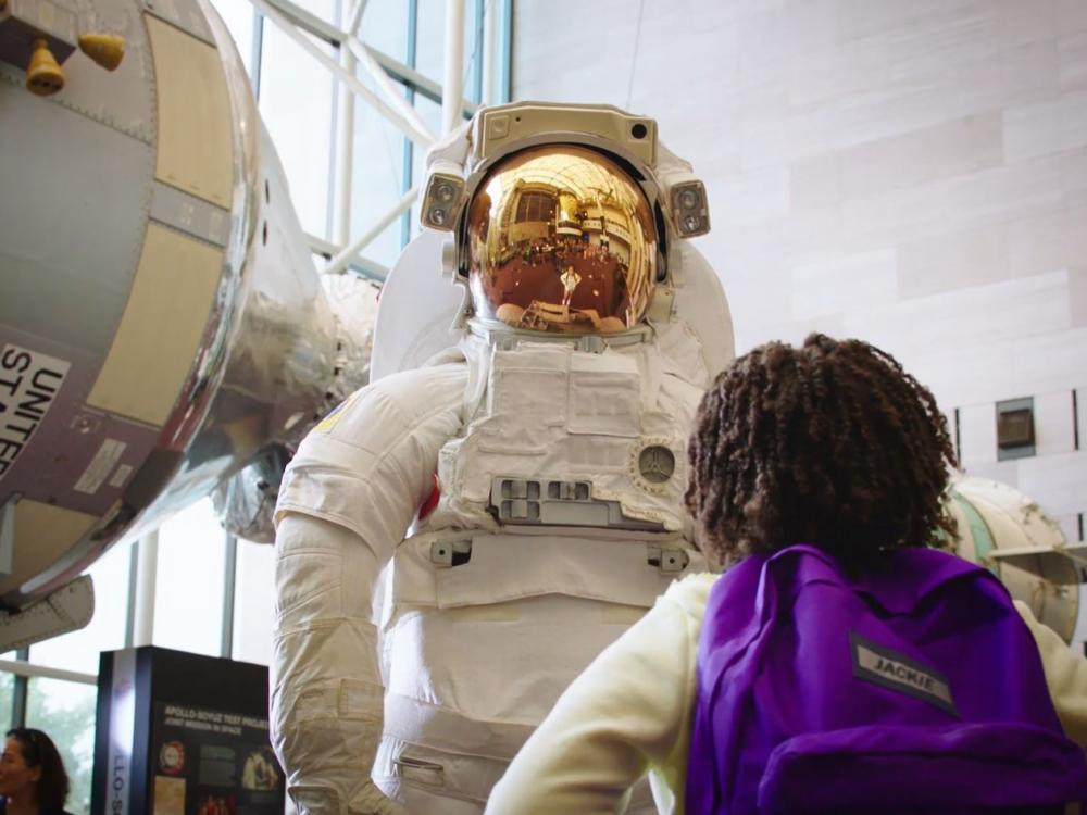 Girl looking up at astronaut suit model at the National Air and Space Museum.