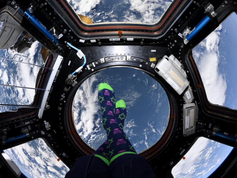 Floating above the Earth, an astronaut posts a picture of her feet in Hanukkah socks.