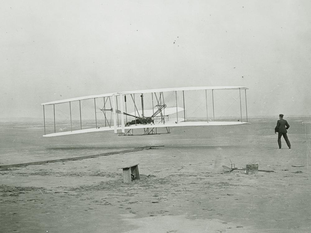 Black and white historic photo of Wright Brothers' first flight
