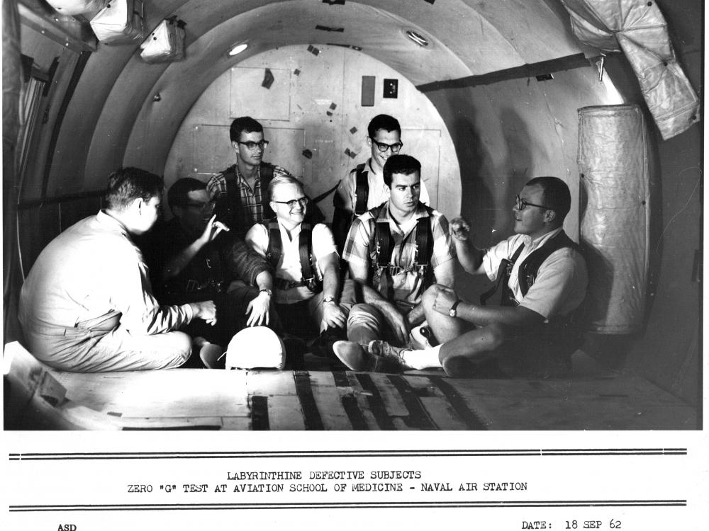 Seven men sit in a tube-like structure.