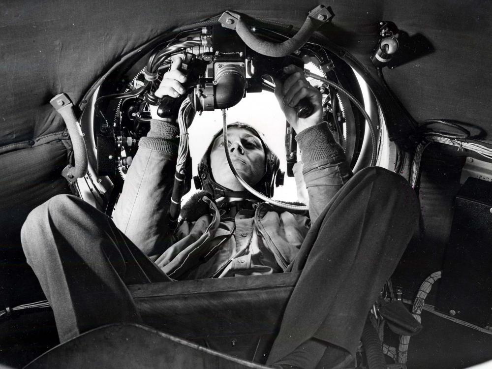 Airmen in gunner's seat in aircraft