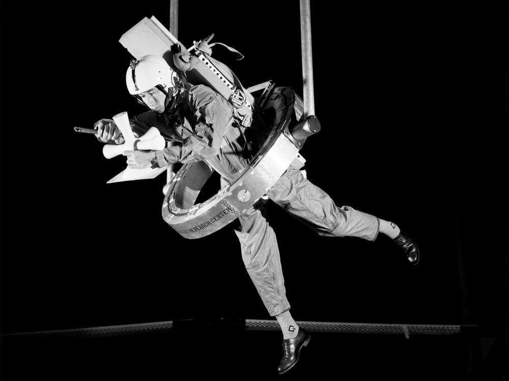 In this black and white image, a man is suspended from an apparatus while using his hands to handle a device.
