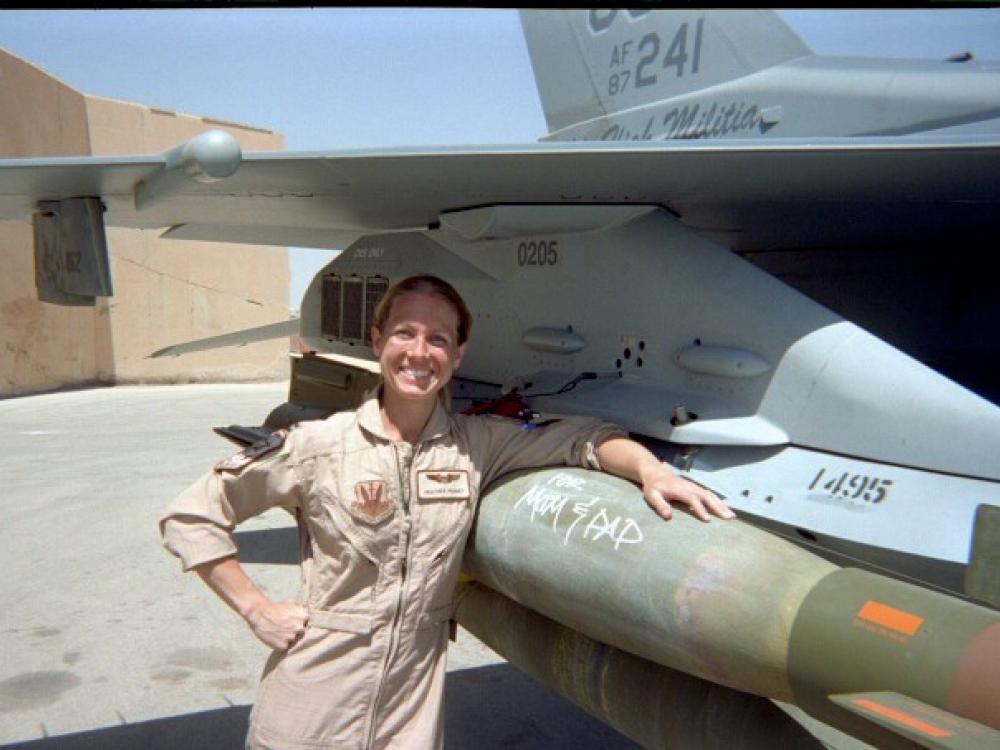 """PilotHeather """"Lucky"""" Penney in front of a plane."""