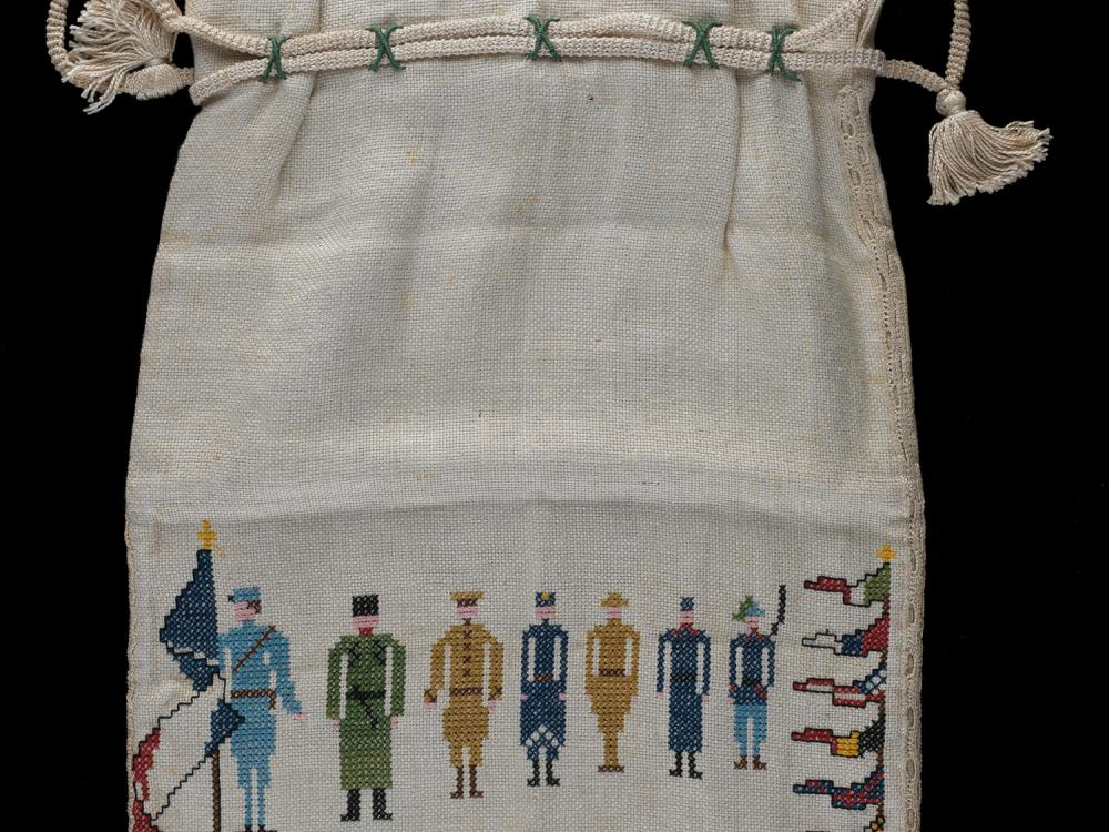 Embroidered bag with line of soldiers and the dates 1914 to 1918.