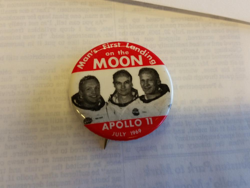 Pin with image of Apollo 11 astronauts in the center and at top and bottom white text against red background.
