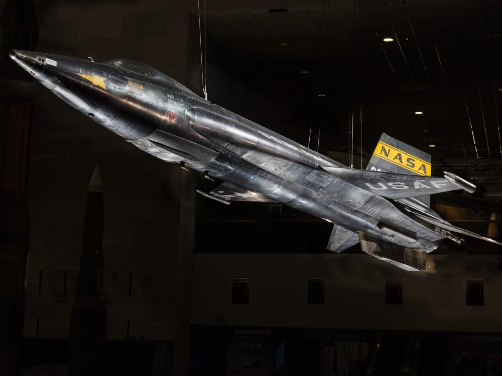 Black titanium rocket-shaped North American x-15 aircraft hanging in museum