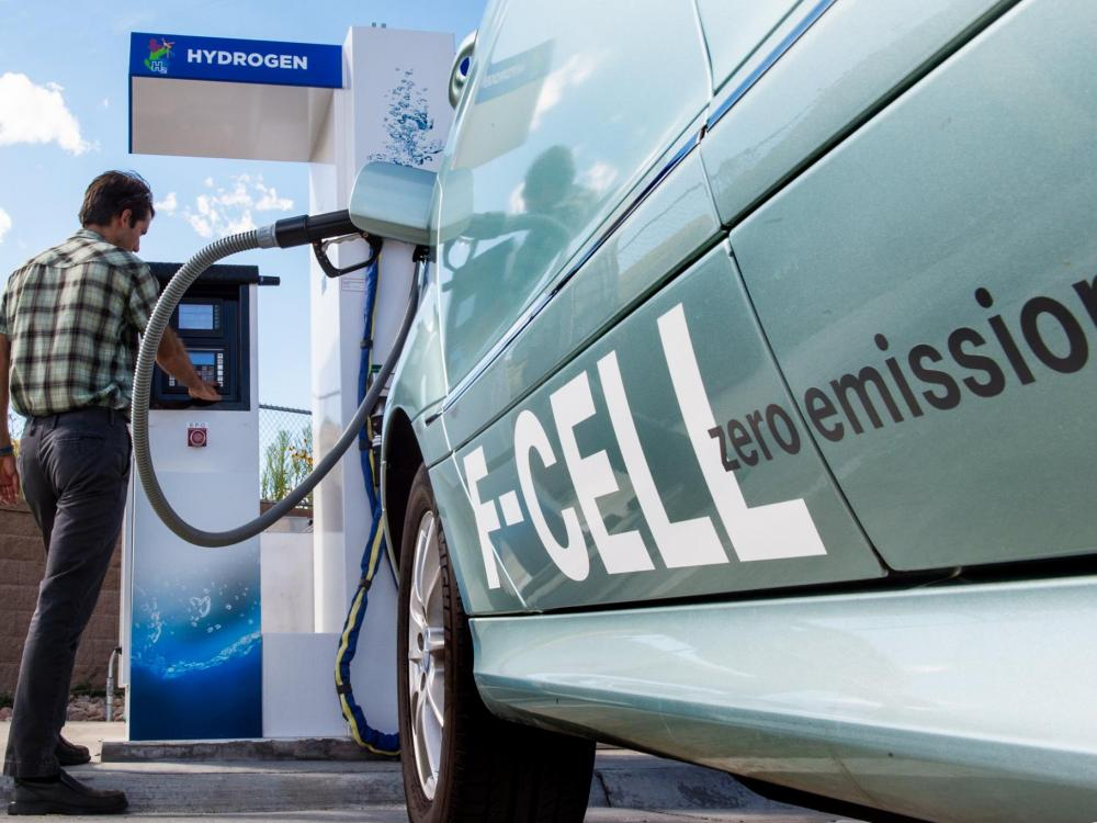 A photo of a fuel cell car being filled at a hydrogen pump.