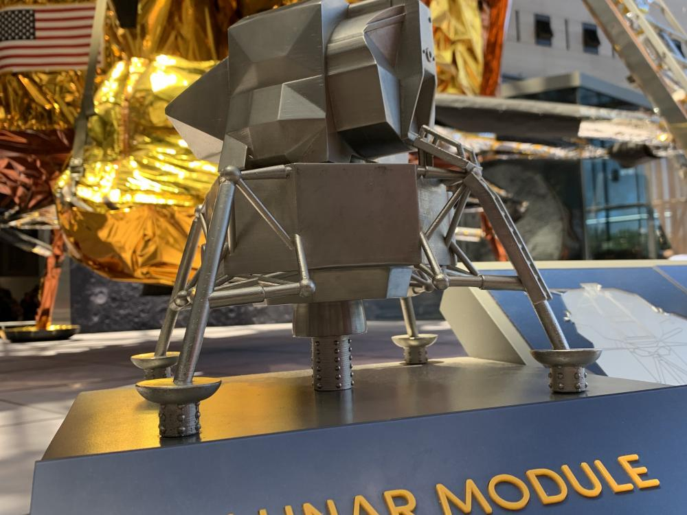 small scale metal version of lunar module with actual lunar module in background