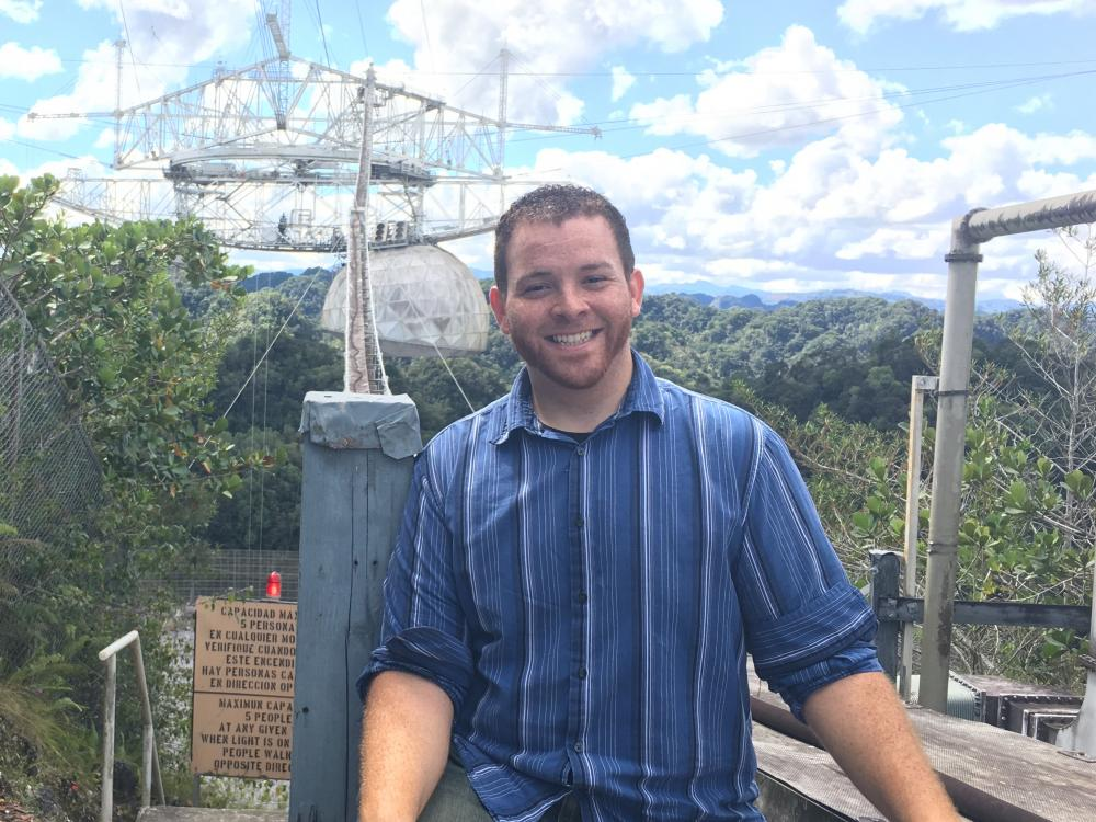 Young person posing for picture with Arecibo Observatory in the background