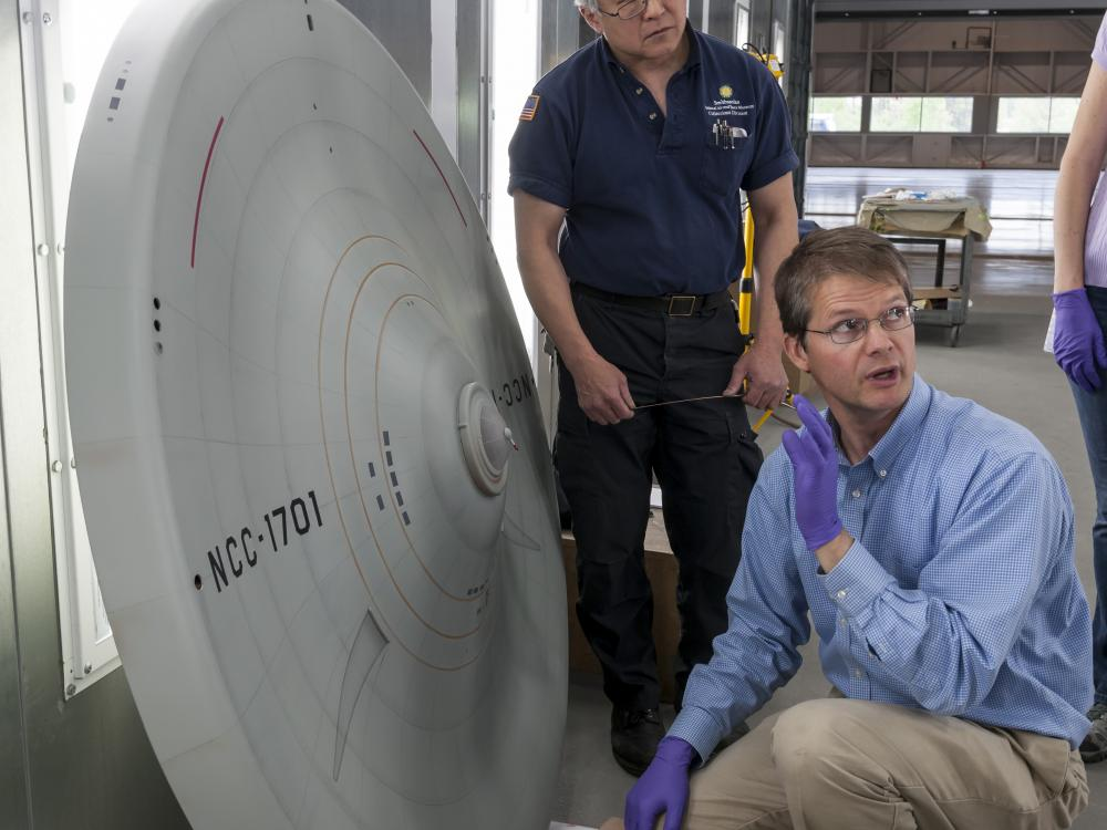 Model saucer on its side while conservators examine it.
