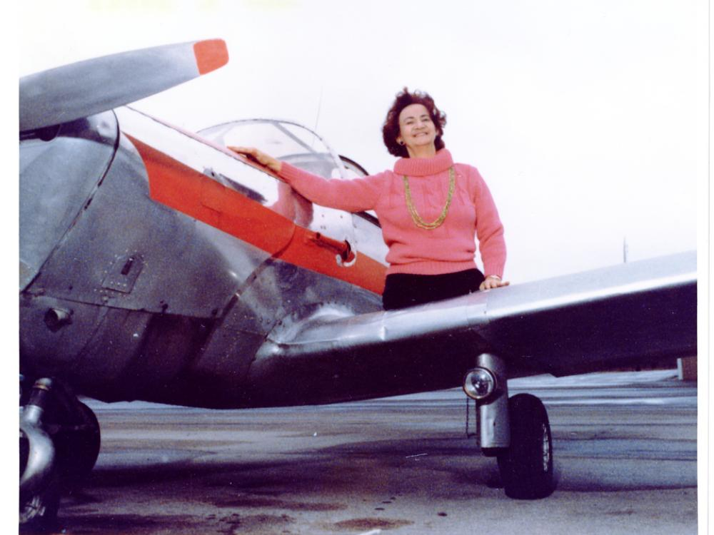A partial view of the left side of an airplane with a white then red stripe under the cockpit. A woman in a pink mock turtleneck sweater with a gold chain necklace sits on the wing of the airplane. She has lost both legs above the knee.