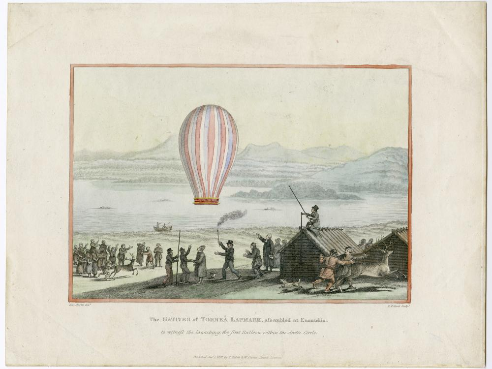 Balloon floats above a small settlement with snow-covered mountains and a lake in the background.