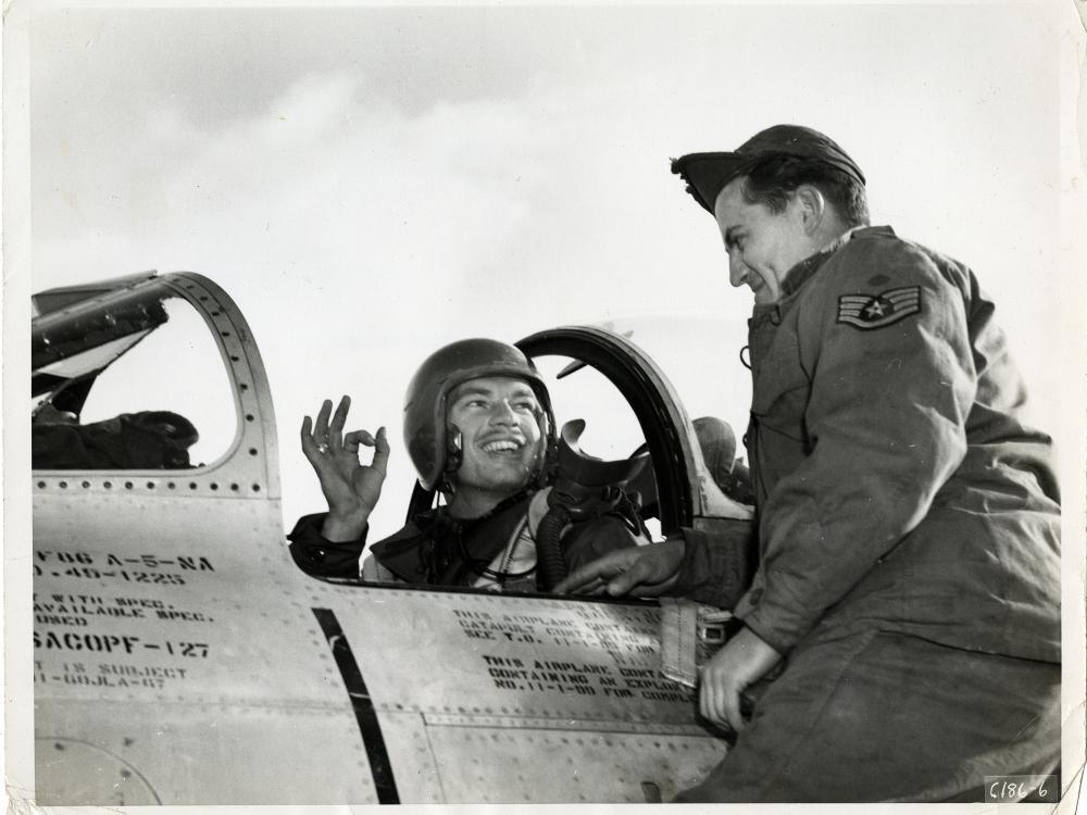 Man in a helmet sits in an aircraft cockpit giving the okay sign with his right hand to a man in a cap and flight suit on his left