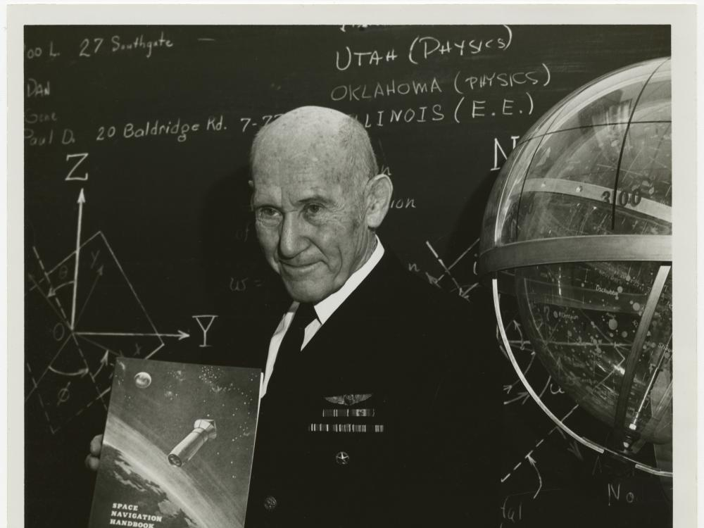 Bald man in Navy uniform stands in front of a blackboard holding a book. Blackboard with chalk writing in the background, Celestial navigation globe partially visible at right.