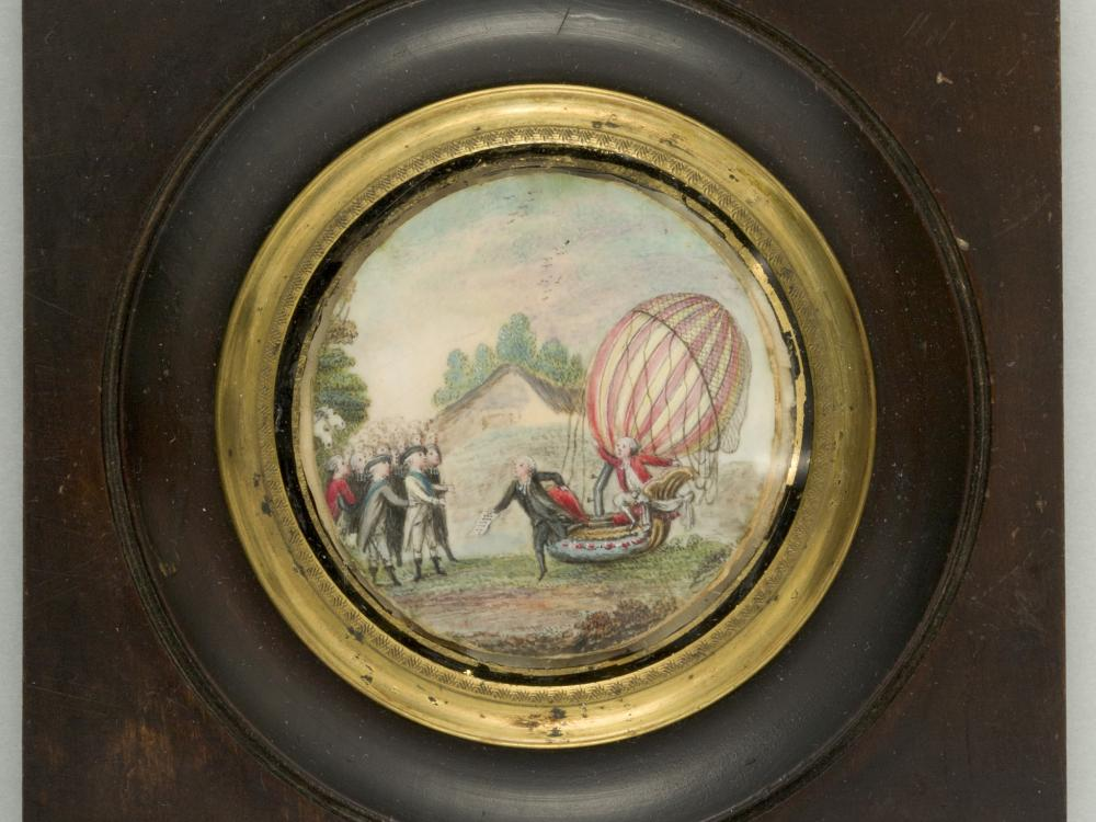 Painting on ivory depicts a balloon on the ground, a man exits the basket, the second man stays in the basket.