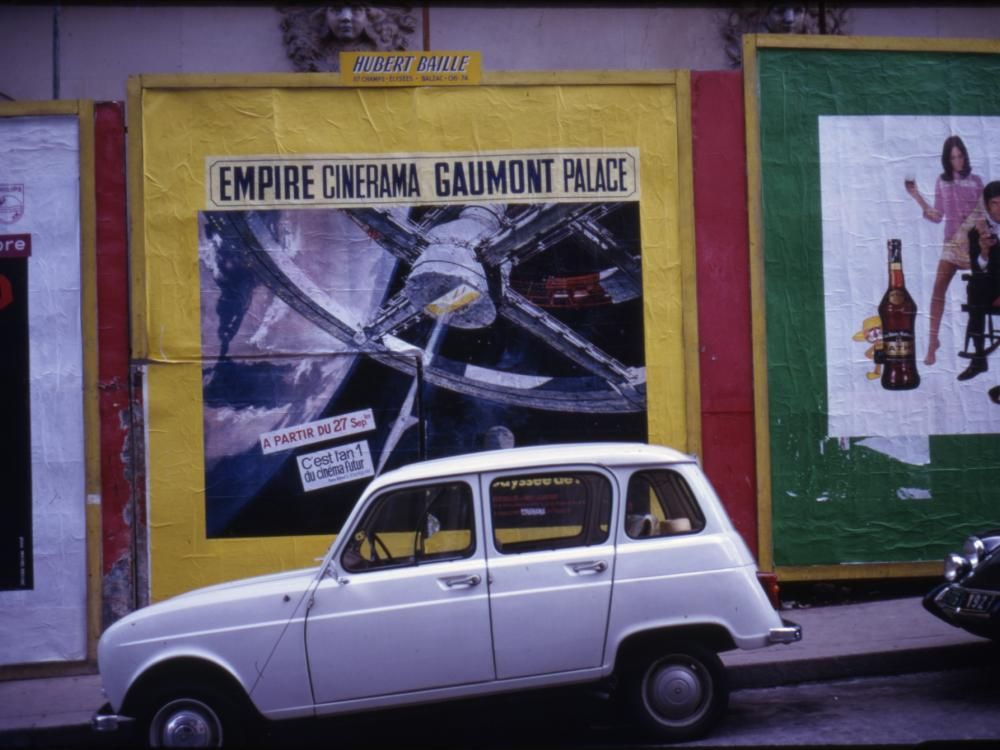"""A white vehicle is parked in front of a movie poster for the film """"2001: A Space Odyssey."""""""
