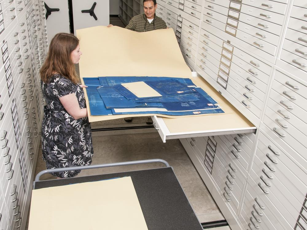 A photo of archivists placing drawings in custom folders and storage.