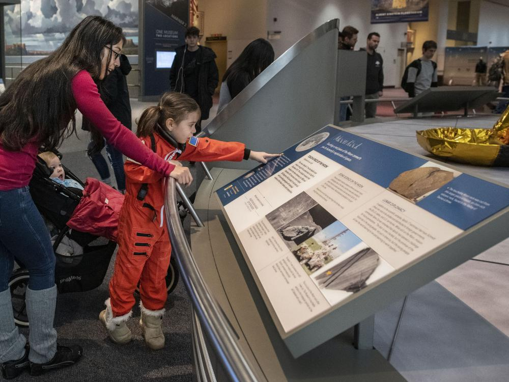 A mother and her children read about the moon rock display in the Boeing Milestones of Flight Hall