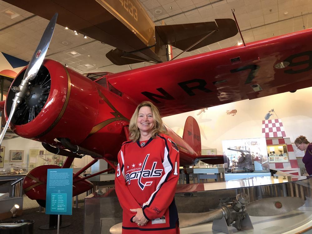 Ellen Stofan wearing a Capitals jersey in front of Lockheed Vega