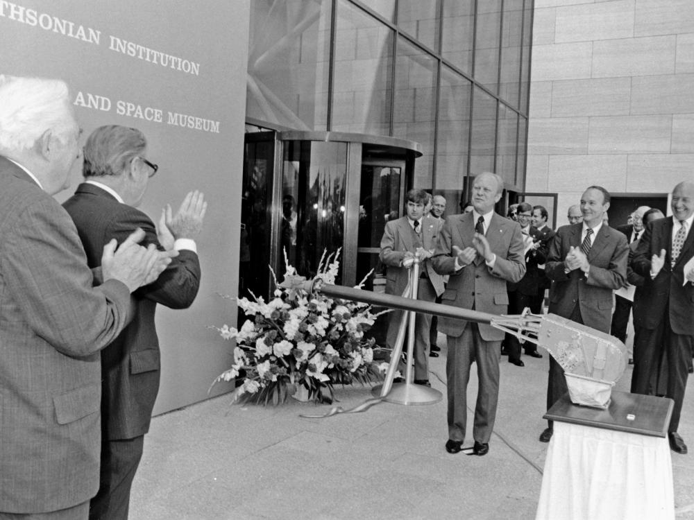 Black and white photo of the ribbon cutting ceremony of the National Air and Space Museum's building in Washington, DC.