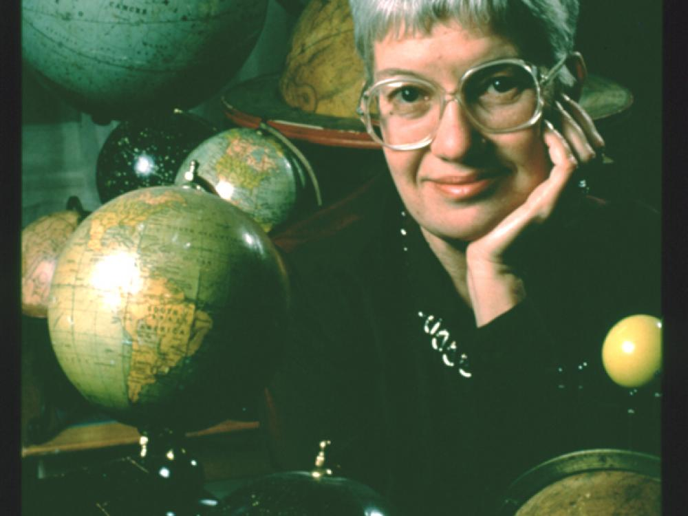 Portrait of Vera Rubin surrounded by her collection of globes.