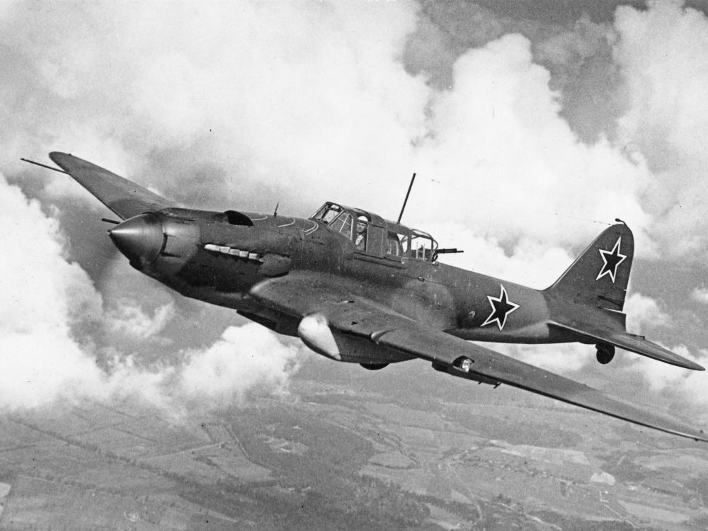 Historical photo of aircraft in flight. Clouds and farmland can be seen in the background.