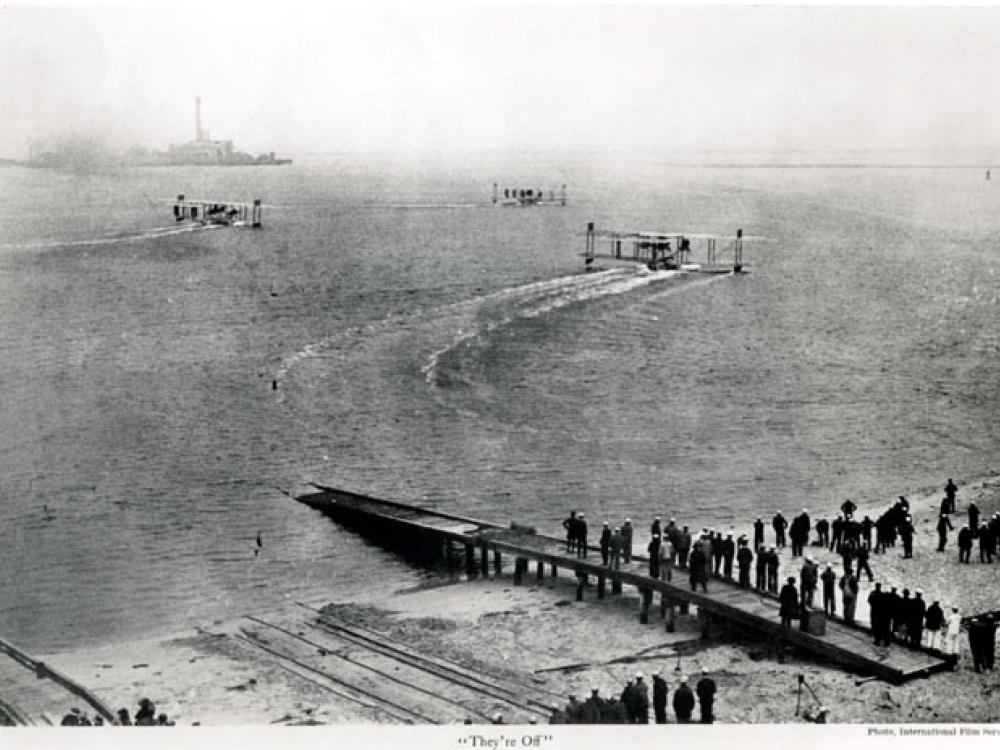 Three aircraft on the water with people on the dock