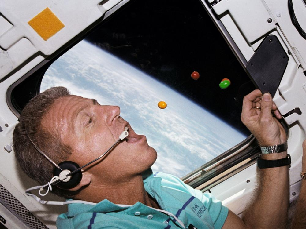 A photo of astronaut Loren J. Shriver eating floating chocolate candies.