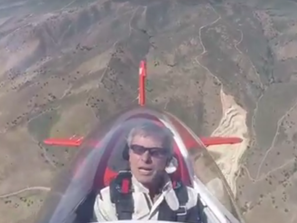 View of Sean Tucker in his red aircraft in flight.