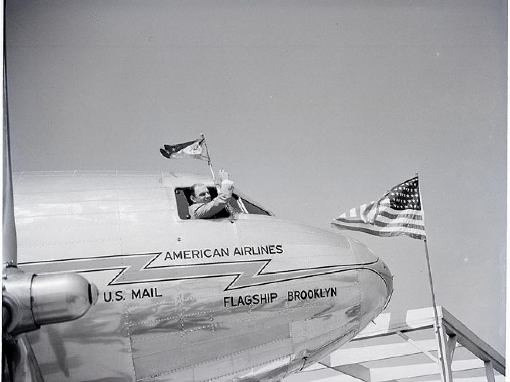 Man waves out the window of a DC-3