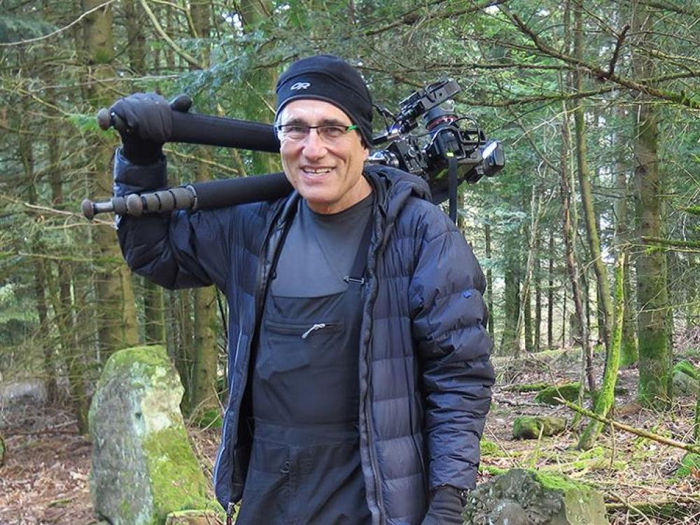 Gusky holds his gear while out in the field.