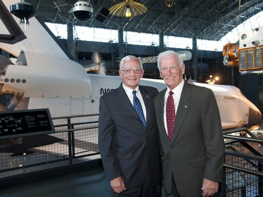 Two men pose in front of space shuttle.