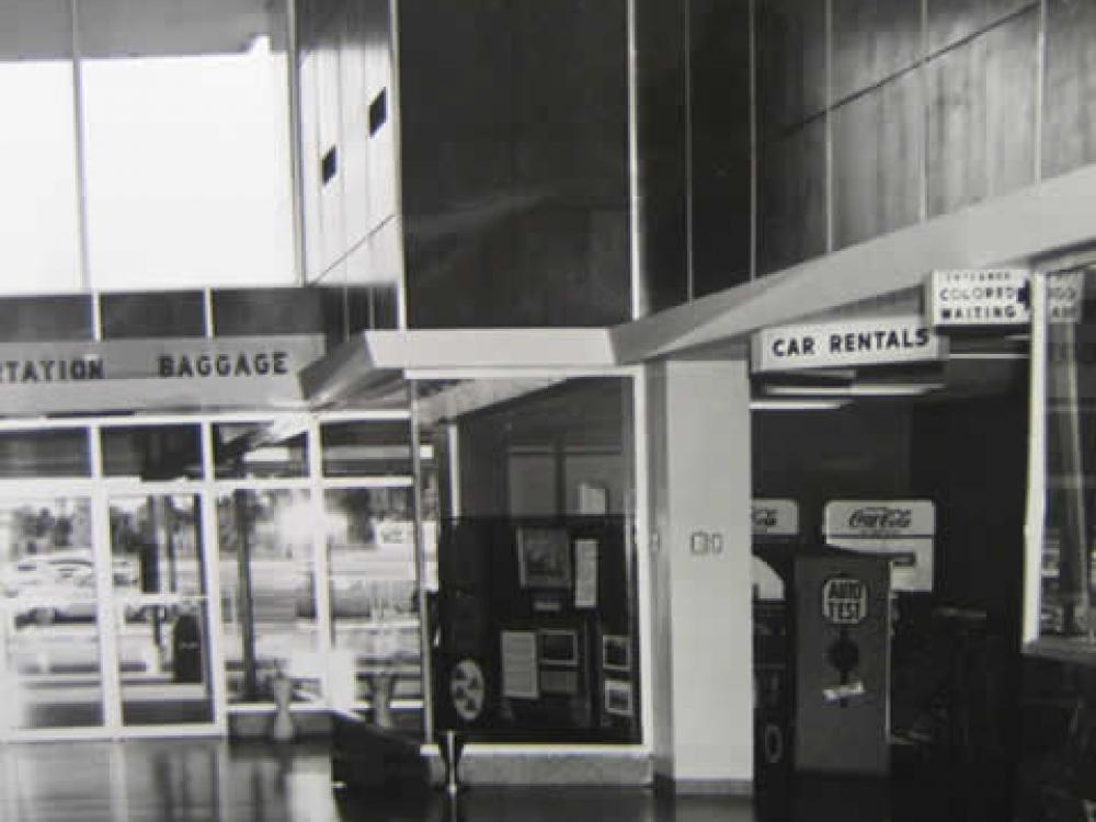 Image of the airport waiting room that shows a sign on right to a sitting area for African Americans.